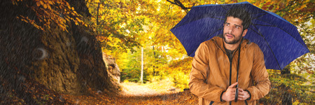 Man standing with blue umbrella against country road along trees in the lush forest Standard-Bild