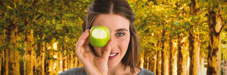 Portrait of young woman holding granny smith apple against walkway along lined trees in the park
