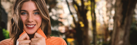 Close up portrait of happy young woman against footpath by trees in city Stock Photo