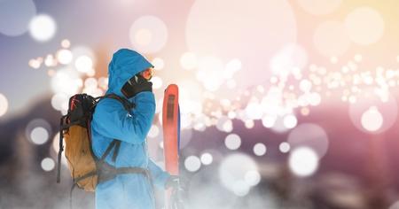 Digital composite of man standing on ski slope calling