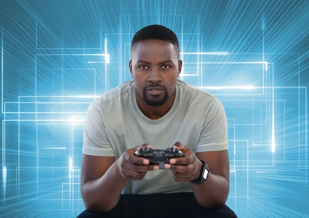Digital composite of Businessman playing with computer game controller with bright light lines background Stock Photo