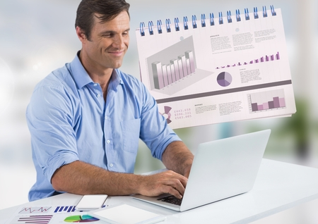 Digital composite of Businessman with laptop at desk with diagrams and charts
