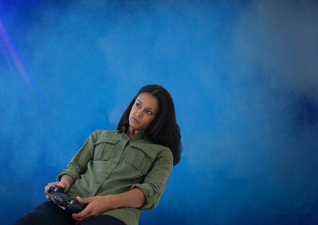Digital composite of Businesswoman playing with computer game controller with blue fog background Stock Photo