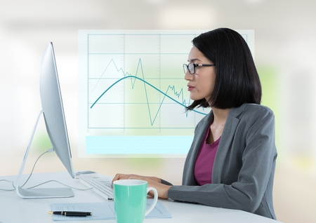 Digital composite of Businesswoman with computer at desk with diagram chart