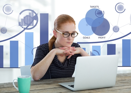 Digital composite of Businesswoman at desk with laptop and bar chart statistics Stock Photo