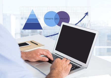 Digital composite of Business hands at desk with laptop and statistic charts