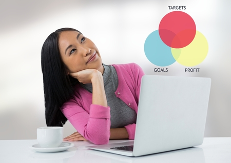 Digital composite of Businesswoman at desk with laptop and target and goals chart Stock Photo