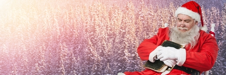 Digital composite of Santa with Winter landscape falling asleep with book
