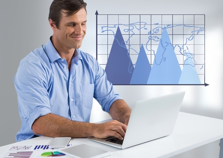 Digital composite of Businessman at desk with laptop and triangle charts with world map on grid