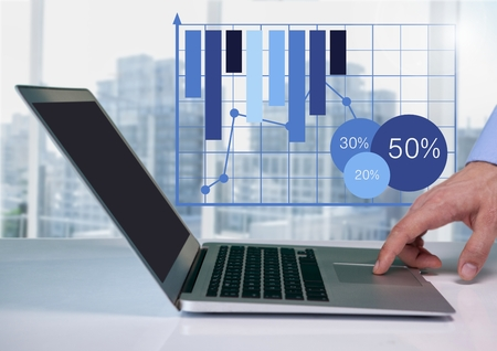 Digital composite of Businessman at desk with laptop and bar chart grid