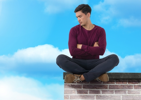Digital composite of Businessman sitting on brick wall