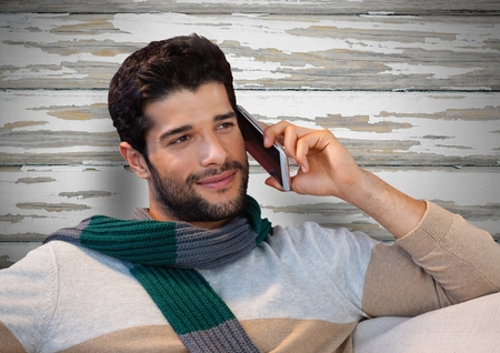 phoning: Digital composite of Man against wood with warm scarf and phone