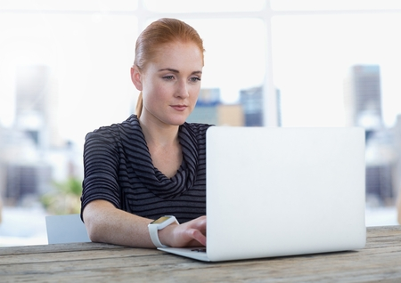 classy house: Digital composite of Businesswoman at desk with laptop with bright background
