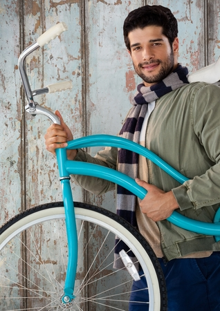 Digital composite of Man against wood with bicycle and warm scarf
