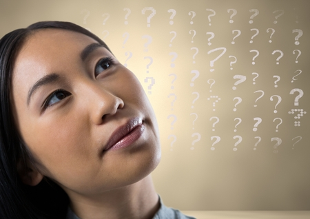Digital composite of woman looking up at question marks
