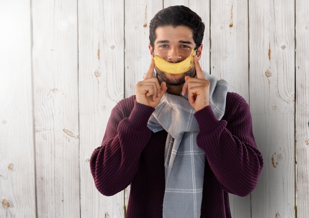 Digital composite of Man against wood with banana and scarf