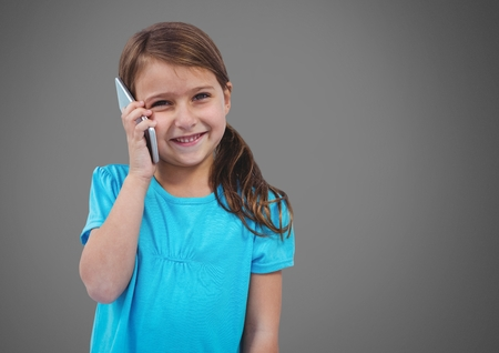 Digital composite of Girl against grey background with phone