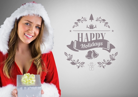 Digital composite of Girl against grey background with Santa Christmas clothes and gift and happy holidays text Stock Photo