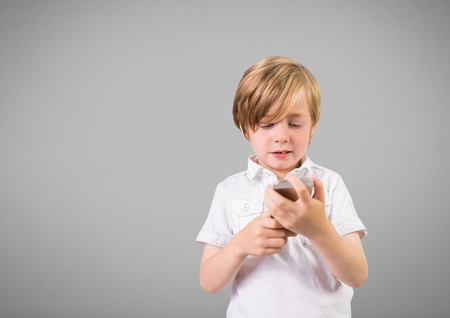 Digital composite of Boy against grey background with phone