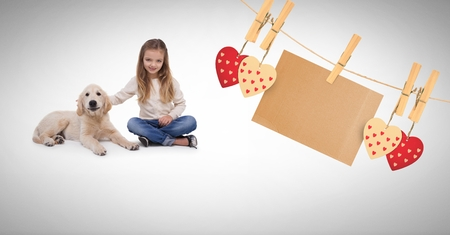 Digital composite of Girl and pet dog with hearts and blank note on pegs Stock Photo