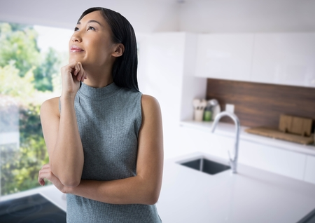 Digital composite of Businesswoman thinking in kitchen Stock Photo