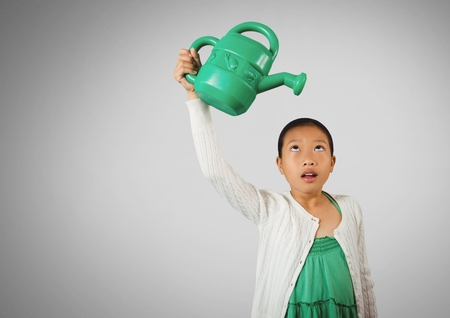 Digital composite of Girl against grey background with Green watering jug 版權商用圖片