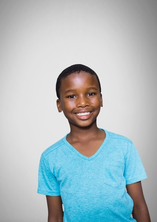 Digital composite of Boy against grey background with blue t-shirt smiling