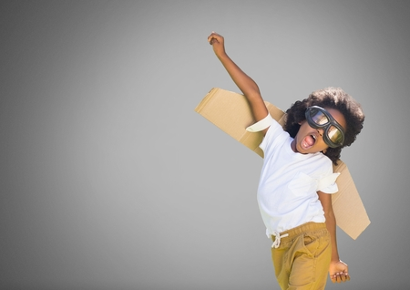 Digital composite of Kid against grey background with cardboard wings Stock Photo