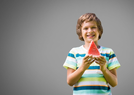 Digital composite of Boy against grey background with watermelon