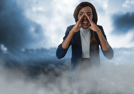 Digital composite of Businesswoman shouting with clouds Stock Photo