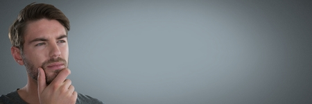 Digital composite of Businessman thinking with grey background