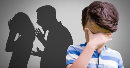 Digital composite of Upset Boy against grey background with shouting fighting parents silhouette