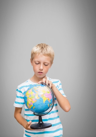 Digital composite of Boy against grey background with world globe