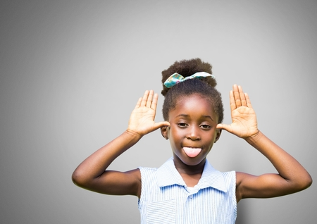 Digital composite of Girl against grey background making funny face sticking out tongue Stock Photo