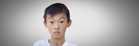 Digital composite of Boy against grey background with bewildered stunned expression