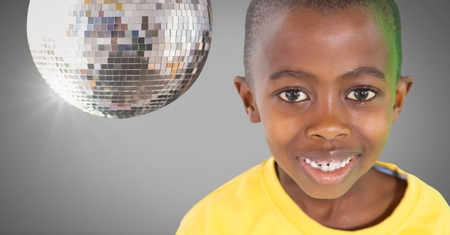 Digital composite of Boy against grey background with disco party ball Stock Photo