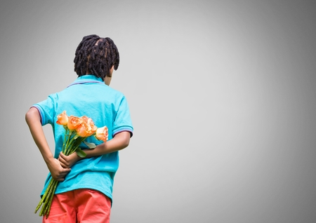 Digital composite of Boy against grey background with bunch of flowers behind back