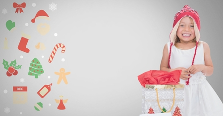 Digital composite of Girl against grey background with Christmas gift bag and Christmas illustrations Stock Photo