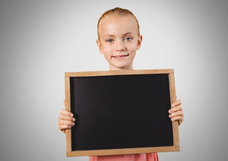 Digital composite of Girl against grey background with blackboard