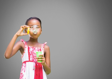 Digital composite of Girl against grey background blowing bubbles 版權商用圖片