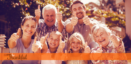 Thanksgiving greeting text against portrait of family gesturing thumbs up Stock Photo