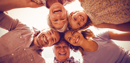 Directly below shot of happy family forming huddle in back yard against sky Stock Photo