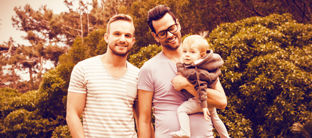 Happy gay couple with child in garden