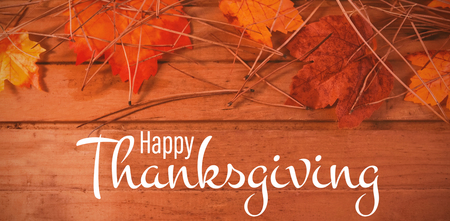 Illustration of happy thanksgiving day text greeting against overhead view of leaves and twigs on table Foto de archivo