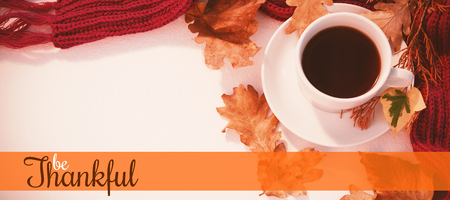 Thanksgiving greeting text against cup of black tea with autumn leaves and woolen cloth on white background Stock Photo