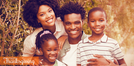 Thanksgiving greeting text against happy family smiling at camera Stock Photo