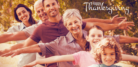 Illustration of happy thanksgiving day text greeting against extended family smiling in park Stock Photo