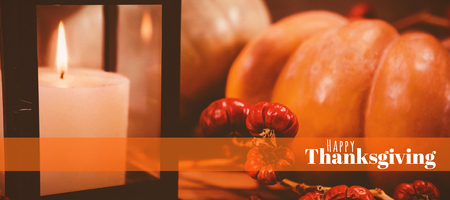 Digitally generated image of happy thanksgiving text against pumpkins by candle on table during halloween