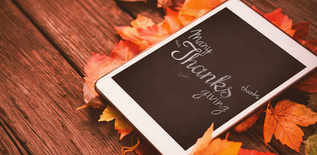 Happy thanksgiving day message against touch pad on leaf on wood table