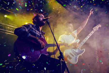 Flying colours against male performers on stage in nightclub Stock Photo